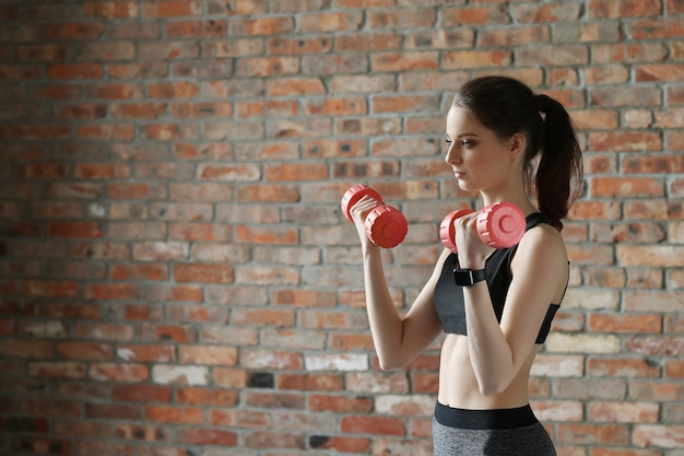 Young sportswoman with dumbbells Free Photo