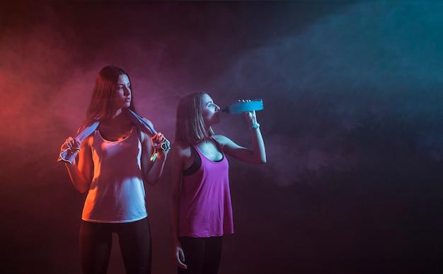 Young sportswomen resting in dark studio Free Photo