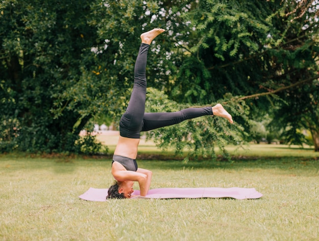 Young sporty attractive woman practicing yoga; doing headstand exercise Free Photo