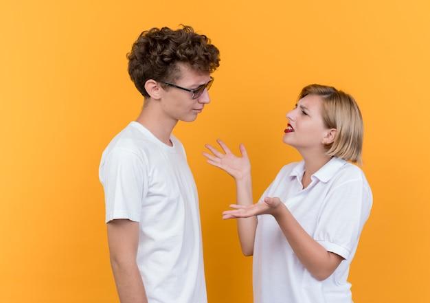 Giovane coppia sportiva uomo e donna che si guardano l'un l'altro discutendo e litigando in piedi sopra la parete arancione Foto Gratuite