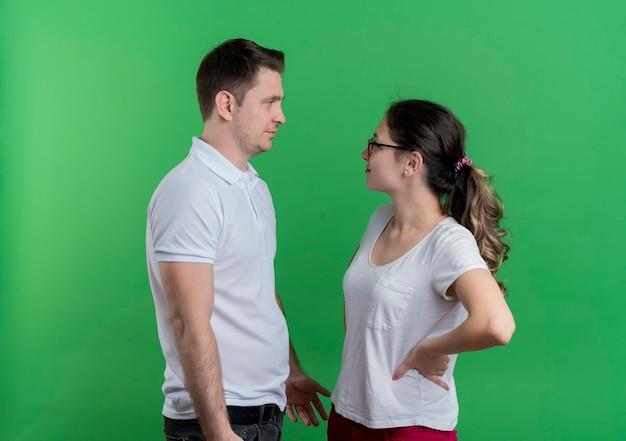 Giovane coppia sportiva uomo e donna che si guardano l'un l'altro discutendo in piedi sopra la parete verde Foto Gratuite