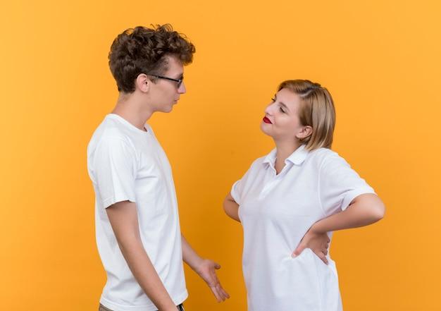 Giovane coppia sportiva uomo e donna che si guardano l'un l'altro discutendo in piedi sopra la parete arancione Foto Gratuite