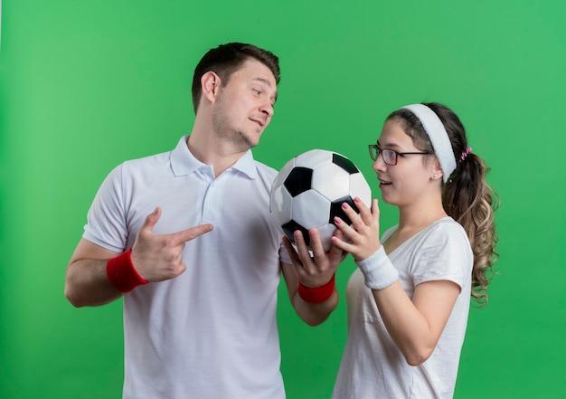 Giovane coppia sportiva uomo e donna in piedi accanto a vicenda tenendo il pallone da calcio oltre la parete verde Foto Gratuite