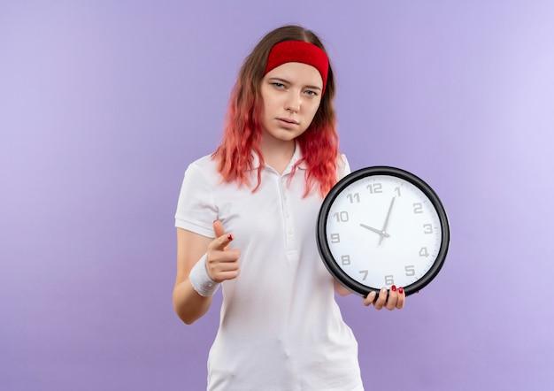 Giovane ragazza sportiva con orologio da parete con viso serio che punta con il dito in piedi sopra la parete viola Foto Gratuite
