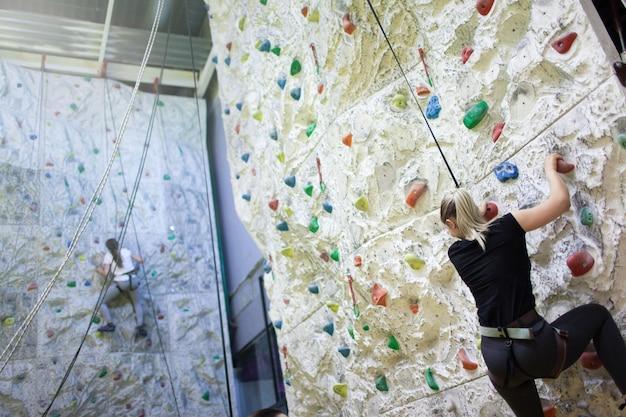 Young sporty girls practicing rock-climbing. Premium Photo