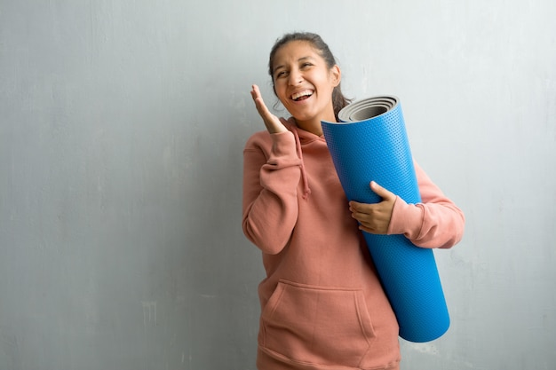 Young sporty indian woman against a wall laughing and having fun, being relaxed and cheerf Premium Photo