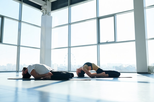 ヨガの練習中に頭で床に触れながら背中を曲げるアクティブウェアの若いスポーティな男女 Premium写真