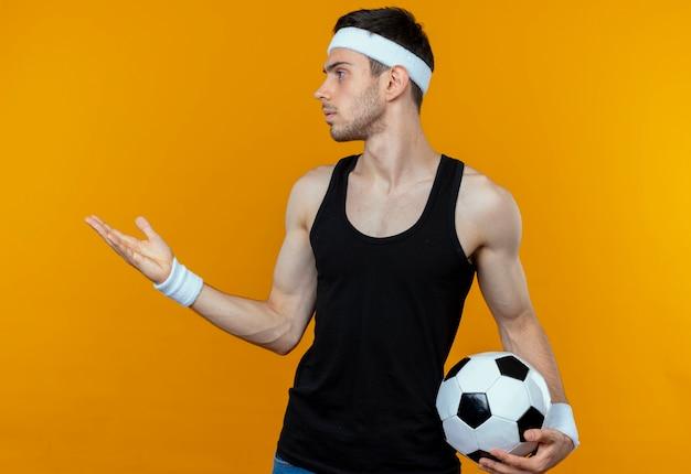 Giovane uomo sportivo in fascia tenendo il pallone da calcio guardando da parte con il braccio fuori come chiedere o discutere in piedi oltre la parete arancione Foto Gratuite