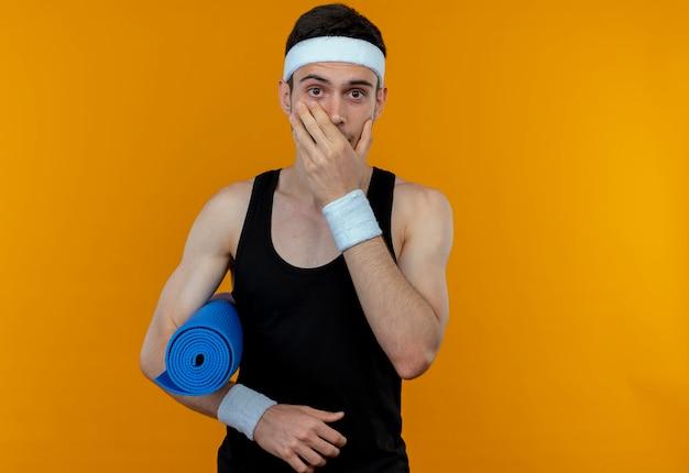 오렌지 벽 위에 서 충격을 받고 손으로 입을 덮고 요가 매트를 들고 머리띠에 스포티 한 젊은이 무료 사진