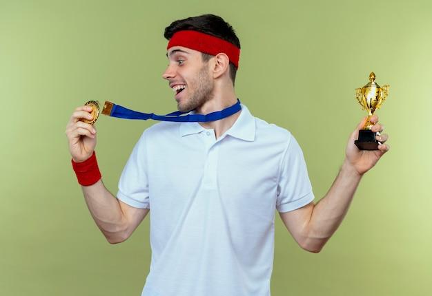 Молодой спортивный мужчина в повязке на голову с золотой медалью на шее держит свой трофей счастливым и взволнованным над зеленым Бесплатные Фотографии