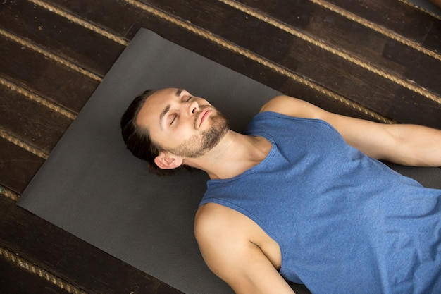 Young sporty man lying in dead body exercise Free Photo