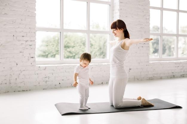 젊은 스포티 한 어머니와 여자 아기 매트에 운동 흰색을 입고 함께 운동, 부모와 자식 건강 개발, 게임, 피트니스 및 휴식 프리미엄 사진