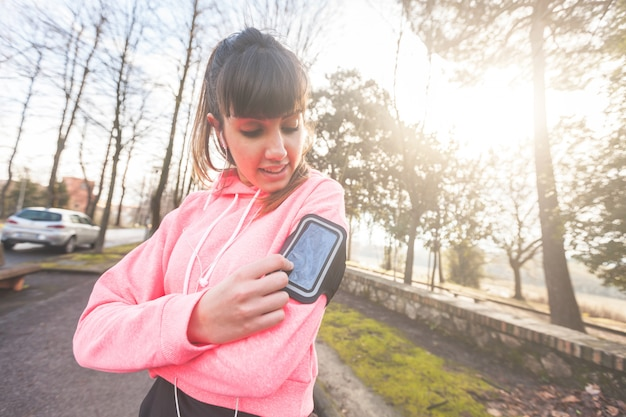 Young sporty woman checking smart phone during workout Premium Photo
