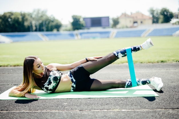 Young sporty woman doing exercises with rubber band outdoor at stadium track. Free Photo