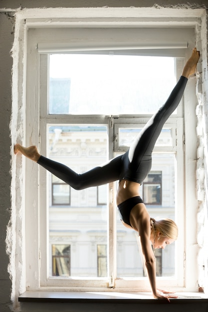 Young sporty woman in downward facing tree pose, window sill Free Photo