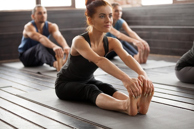 Young sporty woman and a group people in paschimottanasana pose Free Photo