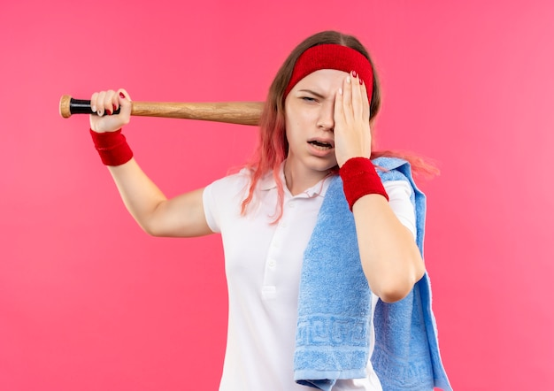 Young sporty woman in headband with towel on shoulder holding a bat looking tired and exhausted standing over pink wall Free Photo