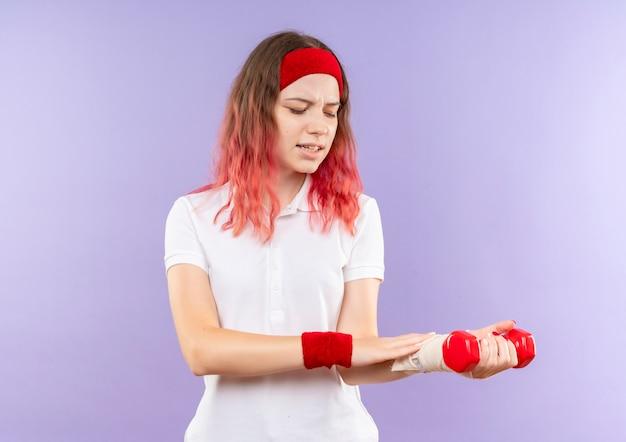 Giovane donna sportiva che tiene due manubri facendo esercizi guardando il suo polso bendato sensazione di dolore in piedi sopra la parete viola Foto Gratuite