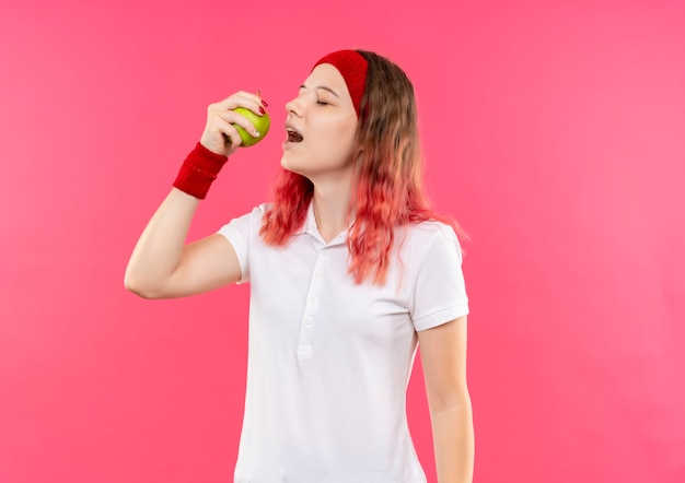 녹색 사과를 들고 머리띠에 젊은 스포티 한 여자가 분홍색 벽 위에 서서 물을 것입니다. 무료 사진