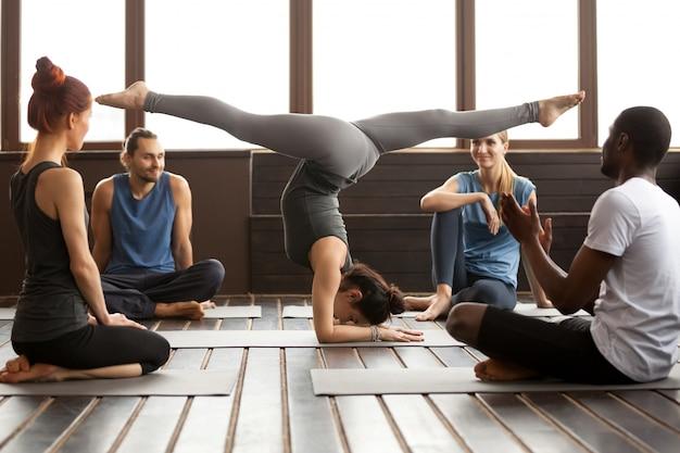 Young sporty woman in pincha mayurasana pose and a group Free Photo