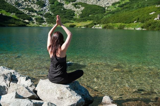 투명한 물과 강이나 호수 근처에 검은 운동복에 요가 연습 젊은 스포티 한 여자 프리미엄 사진