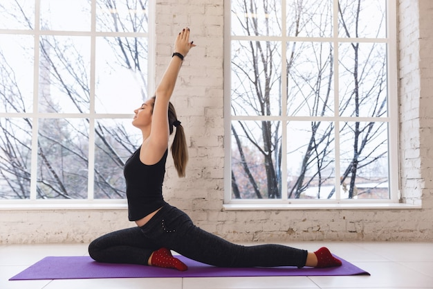 Young sporty woman practicing yoga near the window, doing one legged pigeon exercise Premium Photo
