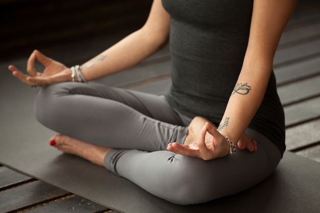 Young sporty woman in sukhasana exercise Free Photo