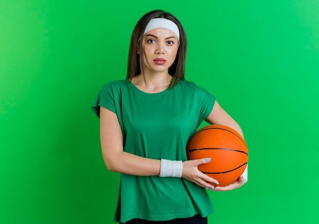 농구 공을 들고 찾고 머리띠와 팔찌를 착용하는 젊은 스포티 한 여자 무료 사진