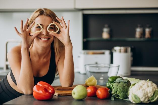 Молодая спортивная женщина с перцем на кухне Бесплатные Фотографии