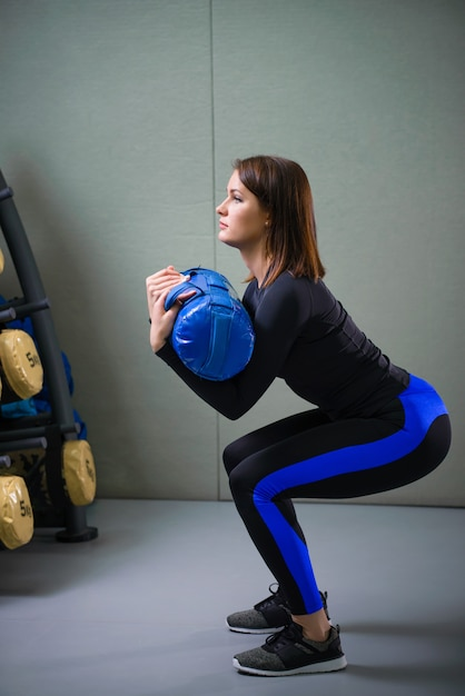 Young sporty woman working out with fitness bag at gym Premium Photo