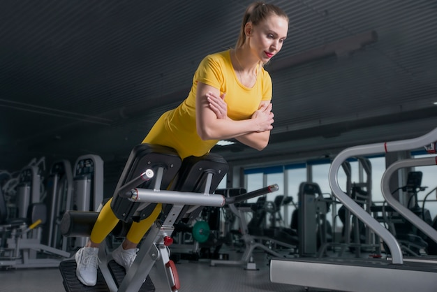 Young sporty woman workout on exercises machine in gym Premium Photo