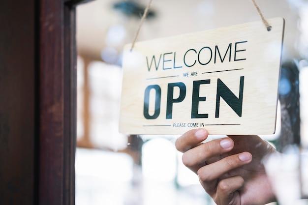 若いスタートアップコーヒーカフェowenerを開いて、顧客を歓迎します。 Premium写真