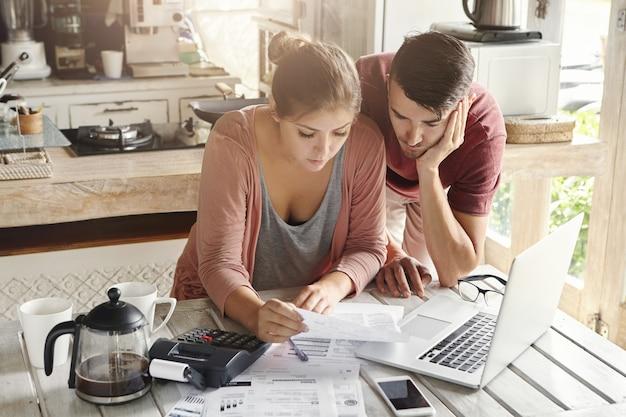 Молодые подчеркнули, что семья оплачивает счета за коммунальные услуги онлайн с помощью ноутбука. обеспокоенная женщина, держащая документ, вместе с мужем рассчитывает внутренние расходы Бесплатные Фотографии