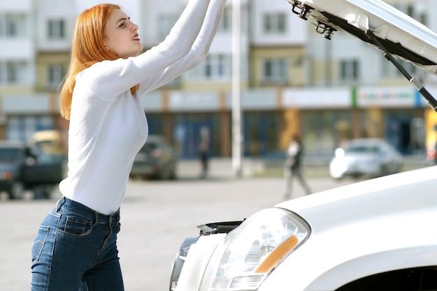 Молодая подчеркнутая женщина-водитель возле разбитой машины с лопнувшим капотом, из-за которой ее автомобиль ждал помощи. Premium Фотографии