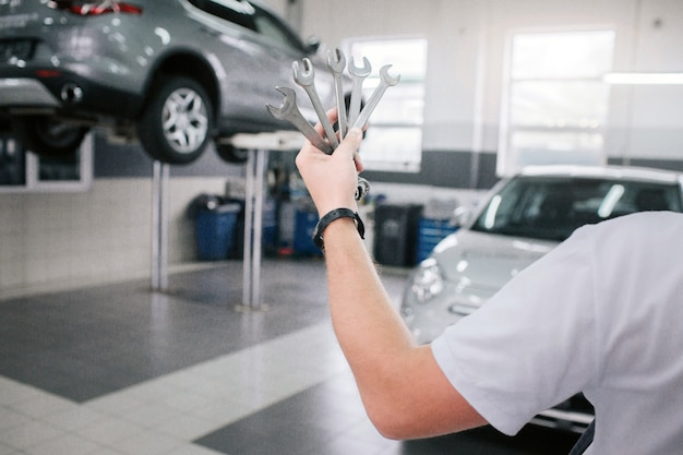 Young and strong man holds set of wrenches in hand. he shows it on camera. man shows it on camera. he stands in front of cars. Premium Photo