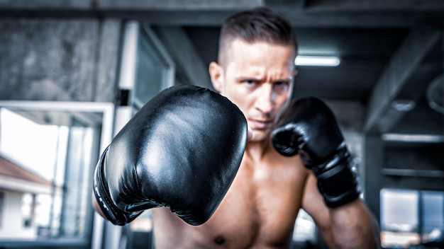 Young strong sports man boxer make exercises in gym Premium Photo