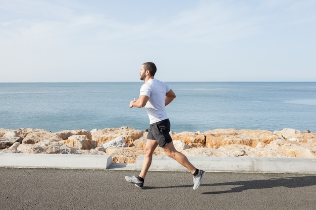 Young strong sporty man running on road along sea Free Photo