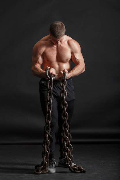 A young strongman is standing with two iron chains holding in his hands Premium Photo