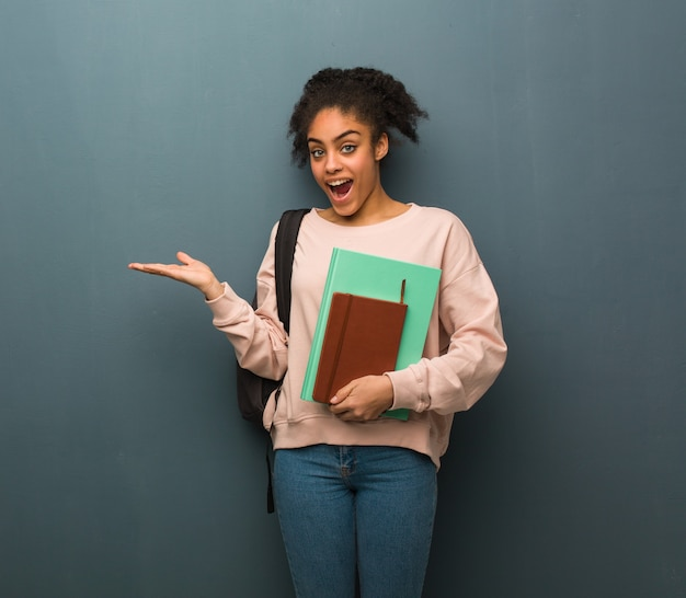 Young student black woman holding something with hand. she is holding books. Premium Photo