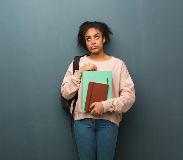 Молодая чернокожая женщина студента устала и скучно. она держит книги. Premium Фотографии
