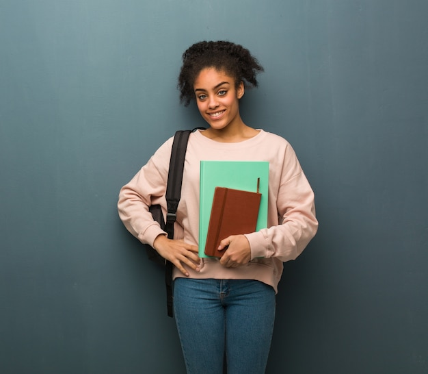 Young student black woman with hands on hips. she is holding books. Premium Photo