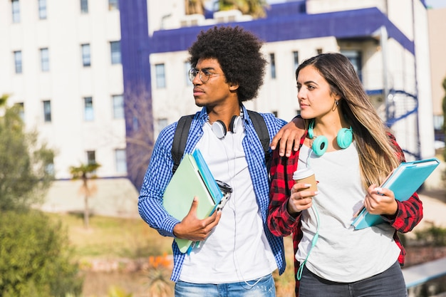 Young student couple holding books and disposable coffee cup standing against campus looking away Free Photo