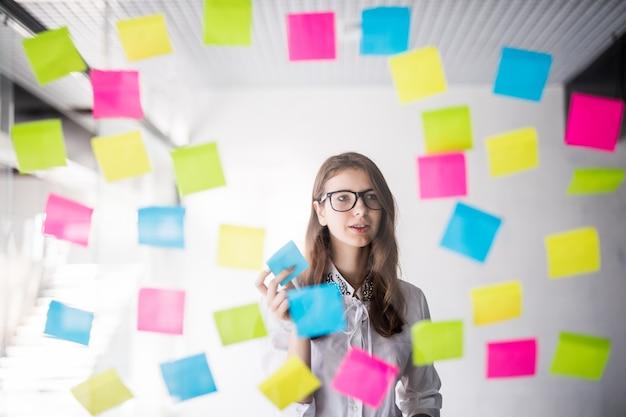 La giovane signora di affari della ragazza dello studente con gli occhiali guarda sulla parete trasparente con molti adesivi di carta su di esso Foto Gratuite
