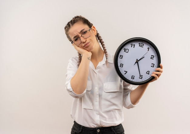 Ragazza giovane studente in bicchieri con le trecce in camicia bianca che tiene l'orologio da parete guardando in avanti stanco e annoiato in piedi sopra il muro bianco Foto Gratuite
