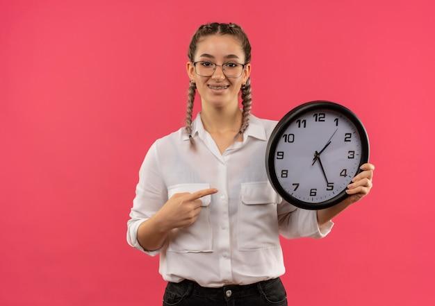 Ragazza giovane studente in bicchieri con le trecce in camicia bianca che tiene l'orologio da parete che indica con il dito ad esso, guardando in avanti sorridente fiducioso in piedi sopra il muro rosa Foto Gratuite