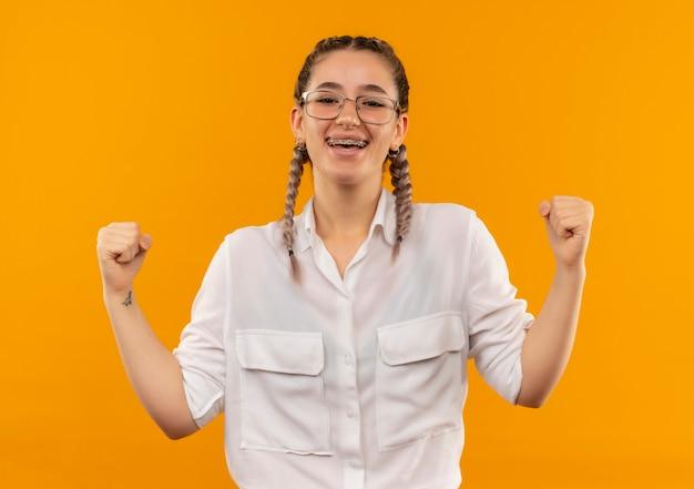 흰 셔츠에 땋은 안경에 젊은 학생 소녀 주먹을 떨림 행복하고 흥분 오렌지 벽 위에 서있는 그녀의 성공을 기뻐 무료 사진