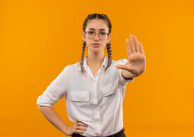 Молодая студентка в очках с косичками в белой рубашке делает знак остановки с рукой, смотрящей вперед, с серьезным лицом, стоящим над оранжевой стеной Бесплатные Фотографии
