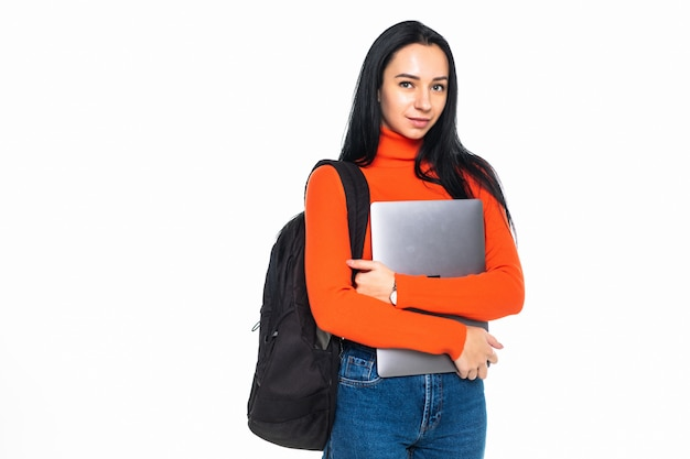 Young student girl isolated on gray wall, smiling at camera, pressing laptop to chest, wearing backpack, ready to go to studies, start new project and suggest new ideas. Free Photo