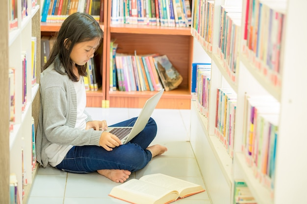 Young student girl sitting  in a library Free Photo