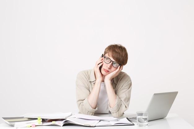 Un giovane studente è seduto al tavolo e ascolta qualcuno al telefono Foto Gratuite
